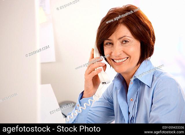 Portrait of smiling senior office worker sitting at desk, using landline phone, looking at camera