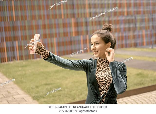woman using smartphone, taking selfie, video conversation
