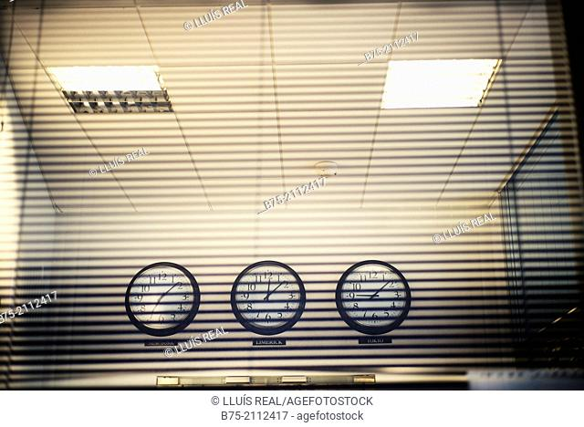 View from the outside of the inside of an office with three clocks hanging on a wall, with different schedules of New York, Limerick and Tokyo