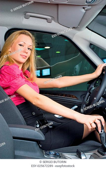 Young pretty woman driving car. Inside view