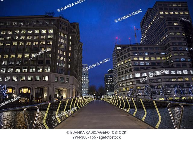 Bridge over water at Canary Wharf financial district at night, Docklands, London, England, UK