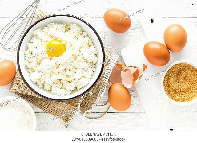 Culinary background with ingredients for cooking, cottage cheese, baking flour, sugar and eggs on white wooden rustic table, top view