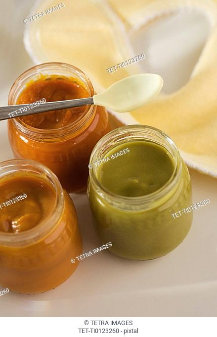 Close up of baby food in jars with spoon and bib