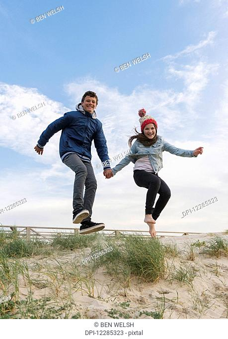 A young man and woman leaping on a beach while holding hands; Tarifa, Cadiz, Andalusia, Spain