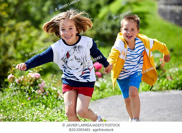 Boy and girl running, holding hands, Getaria, Gipuzkoa, Basque Country, Spain
