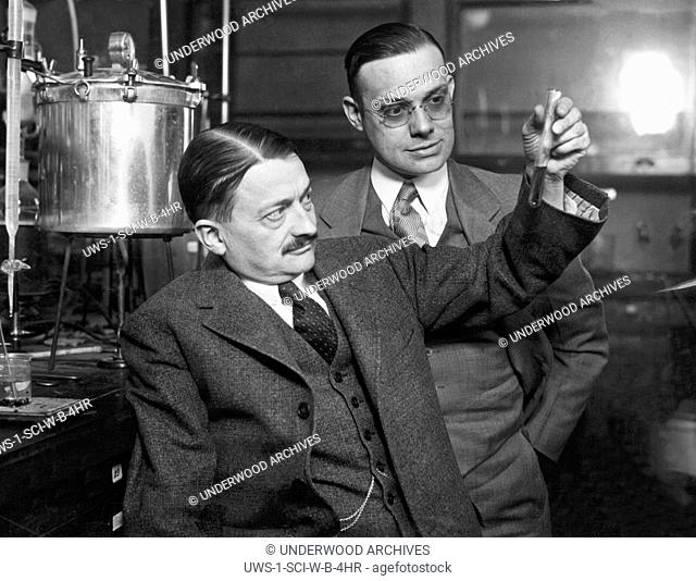 Danville, Illinois: March 8, 1928.Two scientists looking at a test tube containing cornstalk pulp that they hope can be used to replace cellulose in...
