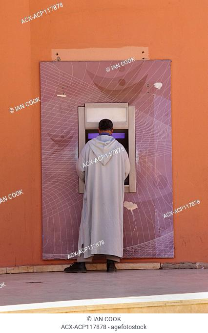 man in traditional dress at a bank machine, Medina, Marrakech, Morocco
