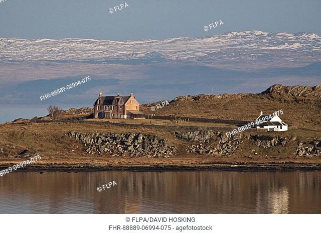House and light house over looking Lowlandman's Bay on the Isle of Jura , The snow covered hill behind are on Kintyre