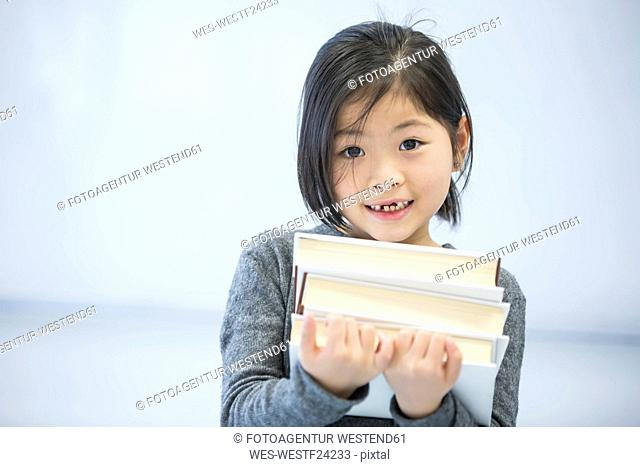Portrait of smiling schoolgirl carrying books in class