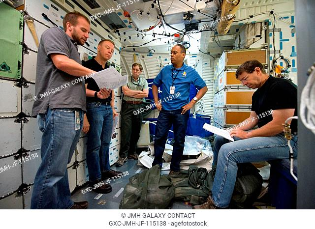Assisted by crew instructors, NASA astronauts Tim Kopra (second left), Alvin Drew (center) and Michael Barratt (right), all STS-133 mission specialists