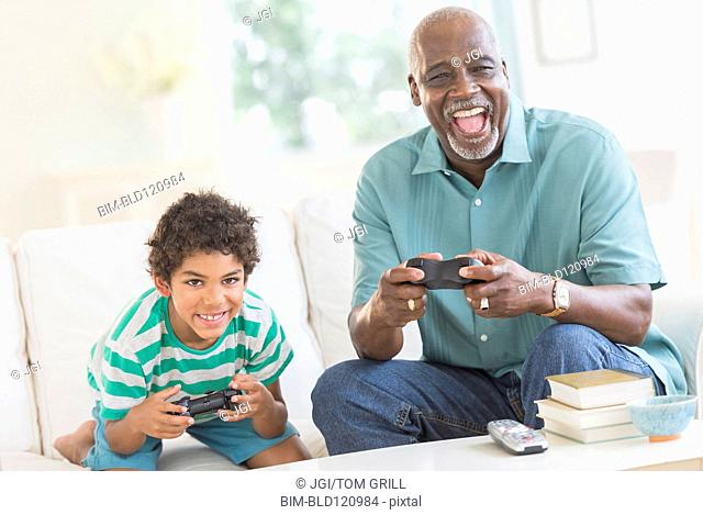 Boy playing video games with grandfather