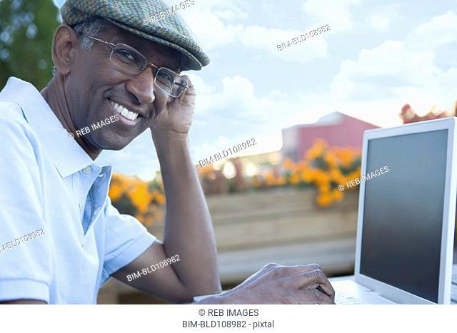 Mixed race man using laptop outdoors