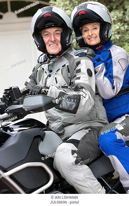 Portrait of happy senior couple wearing helmets on motorcycle
