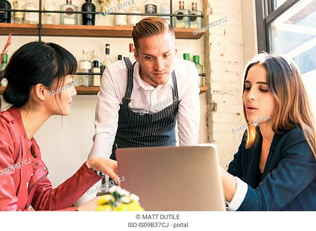 Waiter and female customers looking at laptop in restaurant