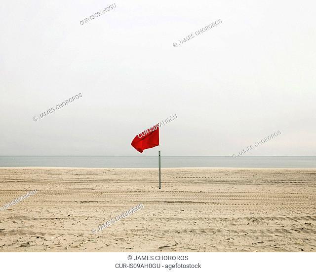 Red flag on empty beach, Coney Island, Brooklyn, New York, USA