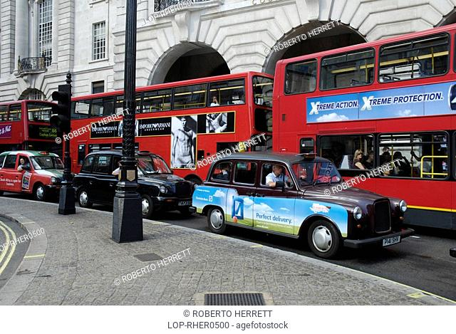 England, London, Piccadilly Circus, Three traditional London taxi cabs and three red London buses with elegant Victorian buildings in the background