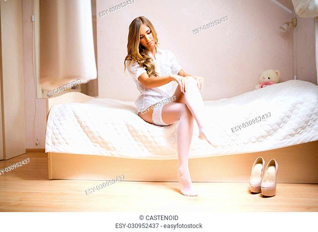 The bride dresses stockings in wedding morning