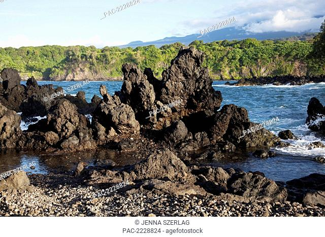 Hawaii, Maui, Keanae, A view of rocky shore in front of lush cliffs