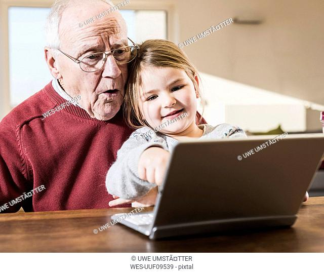 Grandfather and granddaughter using laptop together