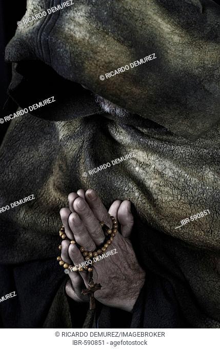 Hooded monk wearing habit, praying