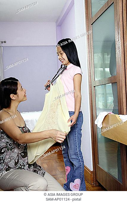 Mother and daughter looking at outfit in bedroom