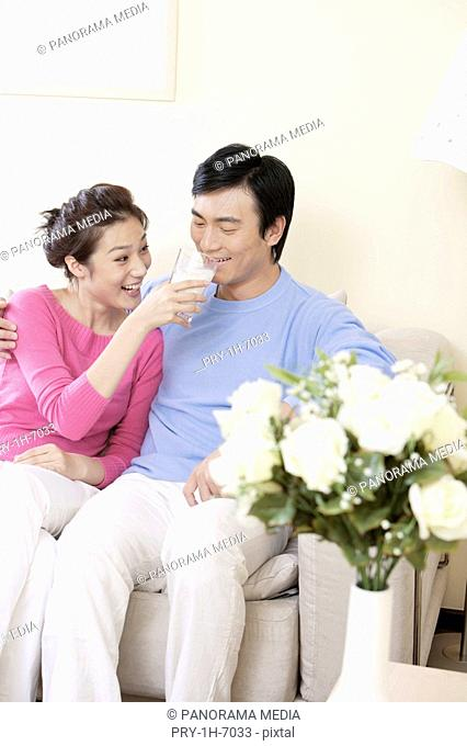Wife feeding glass of milk to husband and smiling