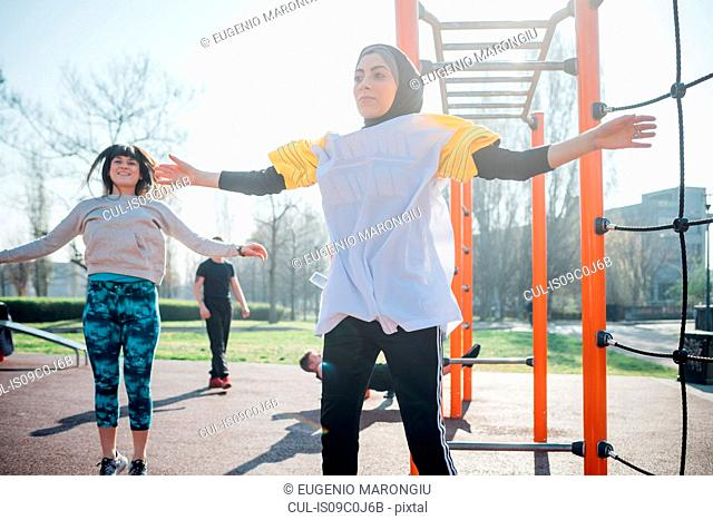 Calisthenics class at outdoor gym, young women jumping with arms outstretched
