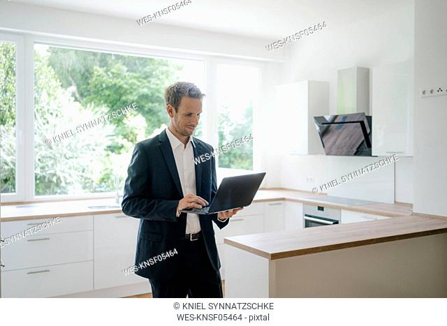 Businessman in newly refurbished home, using laptop in kitchen