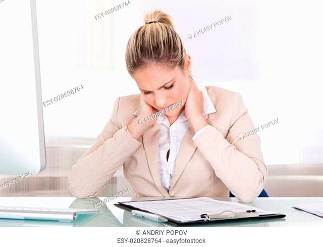 Young Businesswoman Suffering From Neck Pain At Office