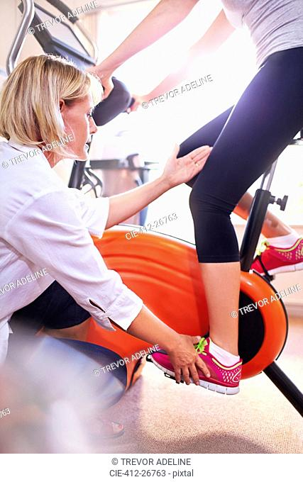 Physical therapist guiding woman's leg on stationary bike