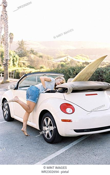 A young woman in denim shorts leaning into a convertible car with a surfboard in the back seat
