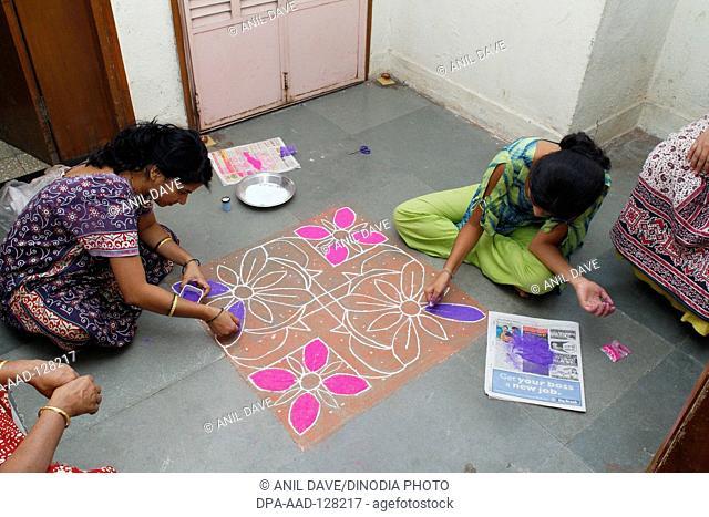 Women filling color in rangoli design on Diwali deepawali festival ; Maharashtra ; India