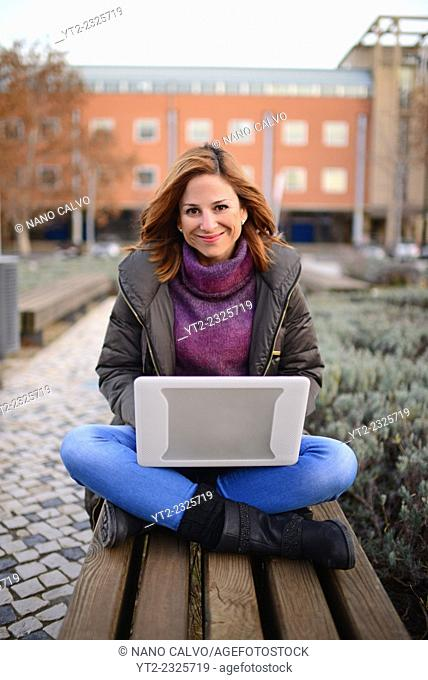 Attractive young woman using laptop outdoors