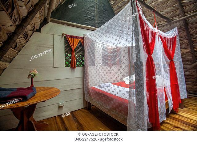 Guatemala, Rio Dulce, Finca Tatin, bedromm with mosquito net bed