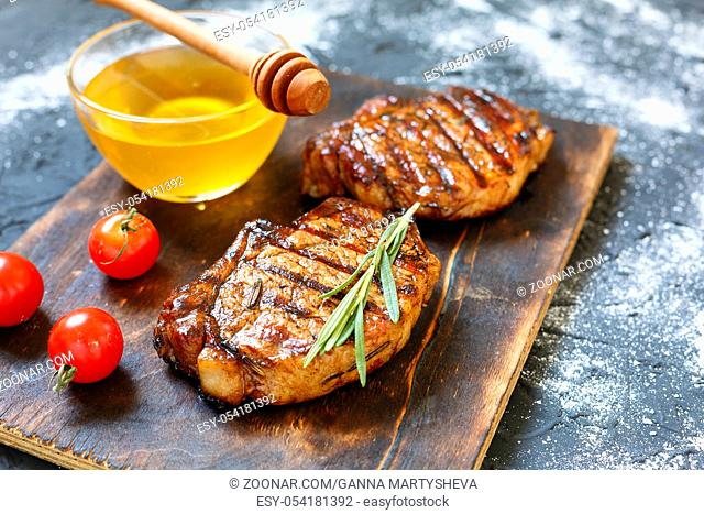 Steak barbecue with ketchup with rosemary closeup. Grilled beefsteaks on cutting board - dinner preparation