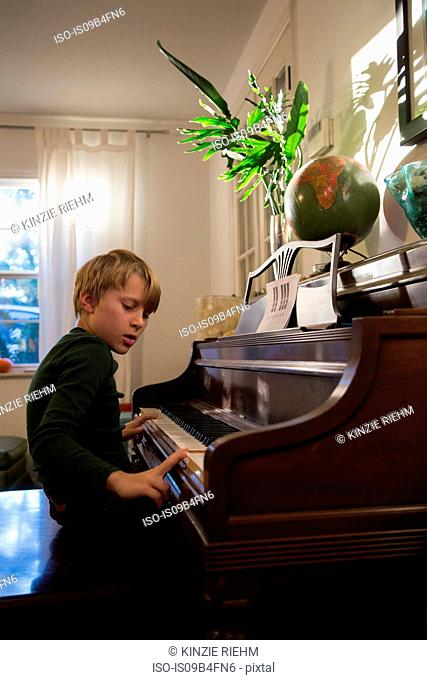 Boy playing piano in living room