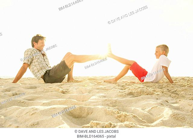 Caucasian father and son touching sandy feet on beach