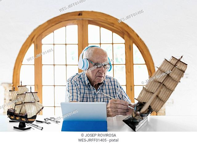 Senior man wearing headphones painting model ship on table with tablet