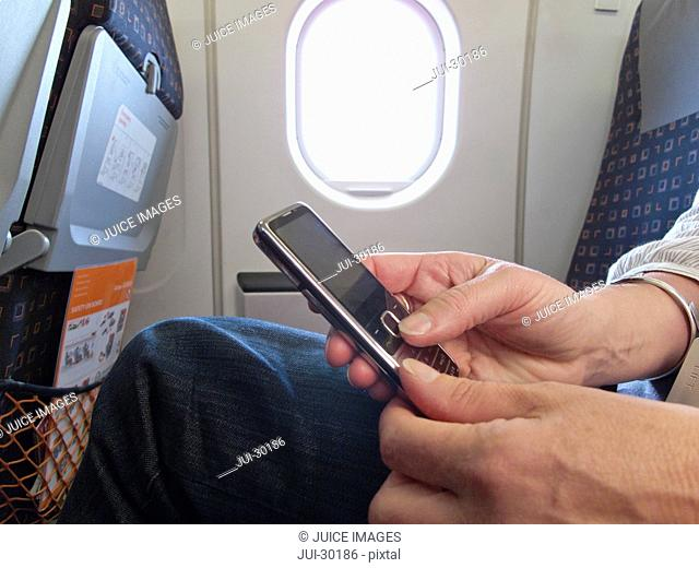 Close up of woman text messaging on cell phone in airplane