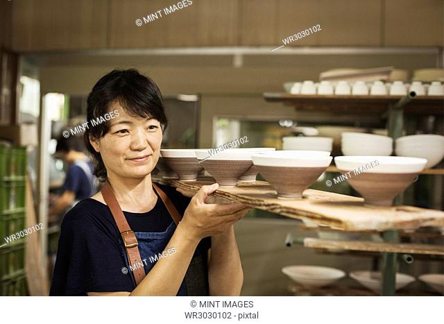 Woman standing in a Japanese porcelain workshop, carrying long wooden tray with bowls