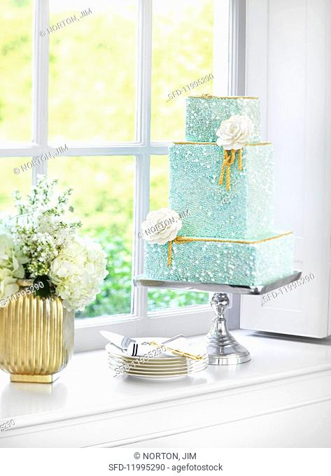 A turquoise three-tiered wedding cake on a silver cake stand in front of a window