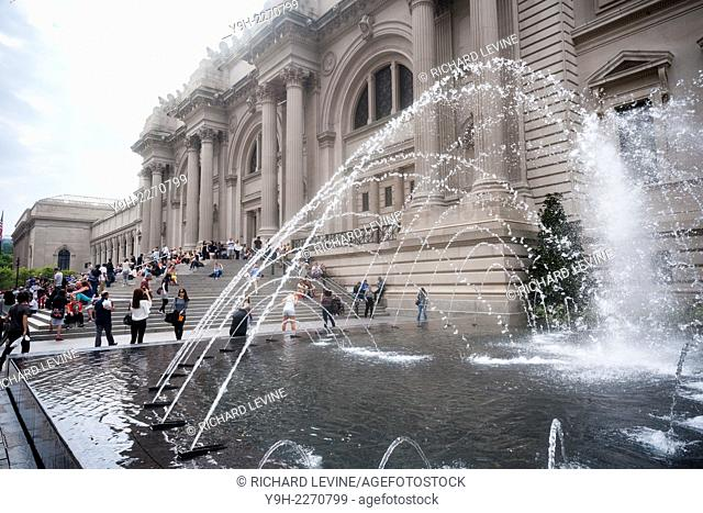 Visitors enjoy the new fountains in the newly renovated David H. Koch Plaza in front of the Metropolitan Museum of Art in New York