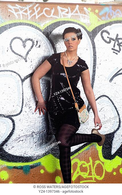 A fashion model in front of a wall covered with graffiti
