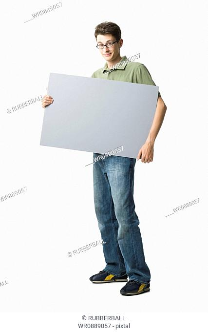 Portrait of a young man holding a blank sign