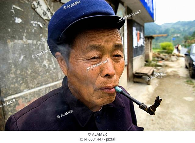 China, Guizhou, Leishan, portrait of a man smoking a pipe
