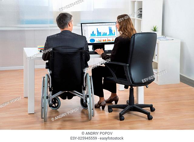 Two Businesspeople Analyzing Statistical Graph On Computer In Office