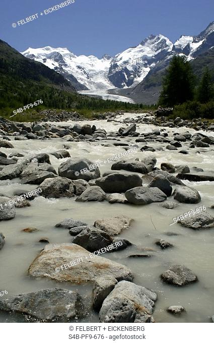 Rivulet with melt water in a valley surrounded by green hills and snowed up mountains
