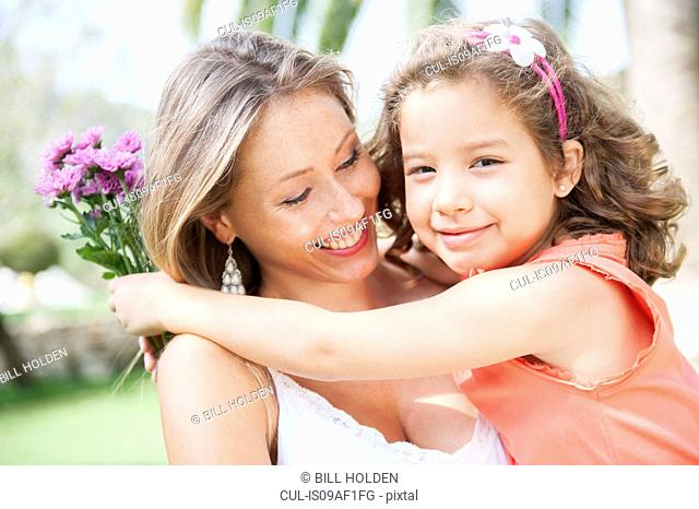 Mother and daughter hugging, holding bunch of flowers