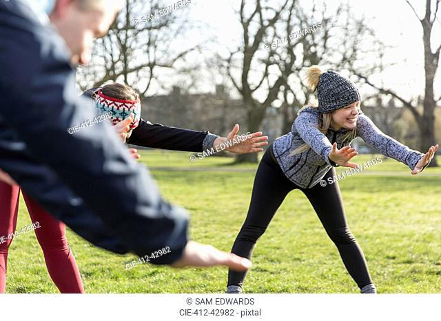 Smiling woman stretching, exercising in park