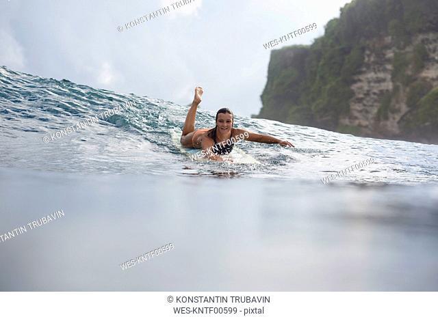 Indonesia, Bali, woman lying on surfboard in the sea